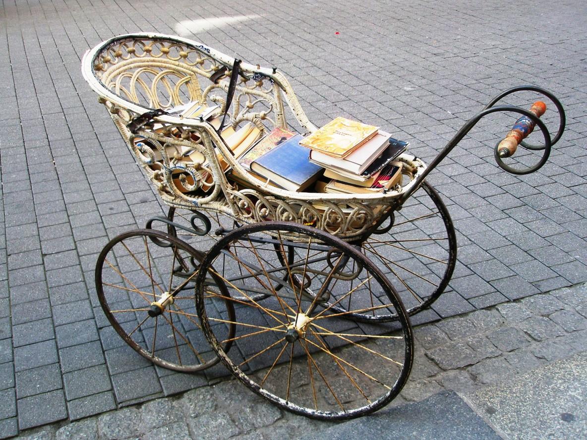 Antiker Kinderwagen gefüllt mit Büchern