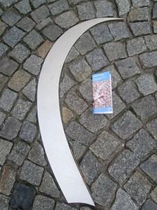 Silberne Markierung im Straßenboden, die die musikalischen Stationen der Notenspur kennzeichnet