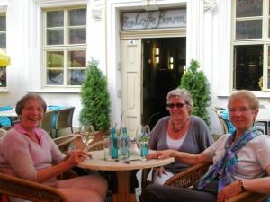 Fröhliche Touristinnen sitzen im Freien an einem Tisch des Lokals Coffe Baum